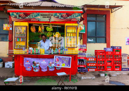 Man selling soft drinks from a brightly coloured street stall in India. - Stock Image