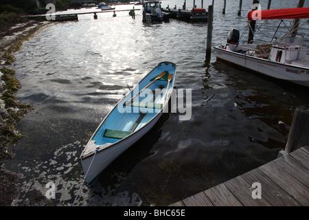 Canoe resting by a dock at Dunewood, Fire Island, NY, USA - Stock Image