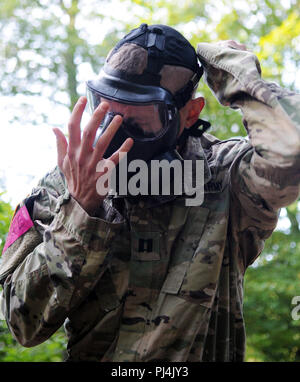 Cpt. Stona Jackson, assigned to Regional Health Command Europe, dons his protective gear during a Chemical, Biological, Radiological, Nuclear event for the 2018 21st Theater Sustainment Command Best Medic Competition August 28, 2018 at Baumholder, Germany.During the second day of the competition competitors encountered a CBRN event, stress shoot, mystery event, and daily non-combat related tasks.#21BMC2018 #FirstInSupport #StrongEurope (U.S. Army photo by Sgt. Benjamin Northcutt 21st Theater Sustainment Command) - Stock Image