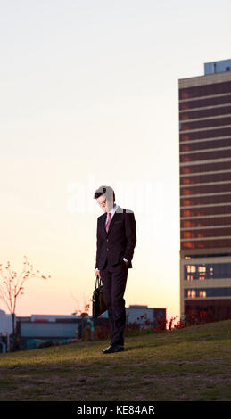 Businessman in city leaving work at sunset - Stock Image