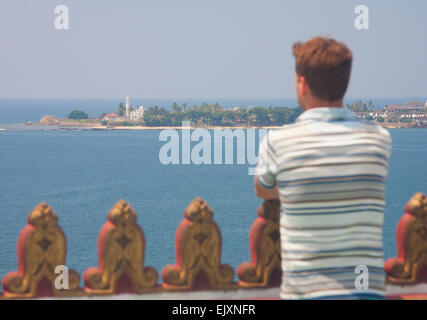 TOURIST AT PEACE PAGODA LOOKING OUT TO GALLE FORT AND MOSQUE - Stock Image