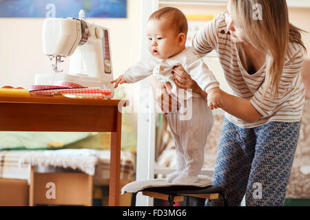 Mother and infant, home, the baby first steps, natural light. Child care combined with work at home. - Stock Image