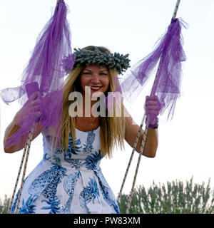 Lady in lavender wreath on the swing - Stock Image