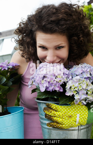 portrait of young woman smelling flowers - Stock Image