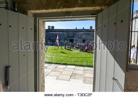 An interior room looks out at a park ranger lecture in the courtyard at the Castillo de San Marcos, a Spanish fortification at St. Augustine, Florida  - Stock Image