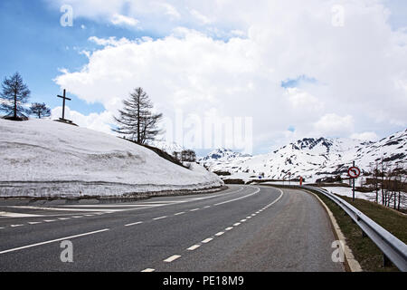 E62 Simplonstrasse road on north side of Simplon Pass in Switzerland with snow banks at the side of the road - Stock Image