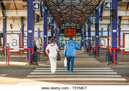 Poznan, Poland - April 18, 2019: Man and woman walking on a zebra crossing in the Rataje bus station. - Stock Image