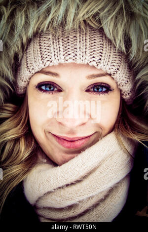 Close up of a woman wrapped up in warm clothing - Stock Image
