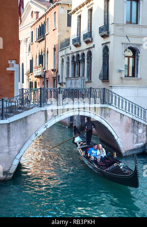Couple taking a romantic gondola ride through the canals of Venice, Italy - Stock Image