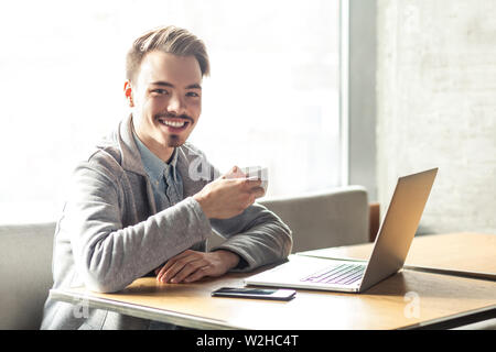 Portrait of handsome happy bearded young businessman in grey blazer are sitting in cafe and have a break with cup of coffee and toothy smile are looki - Stock Image
