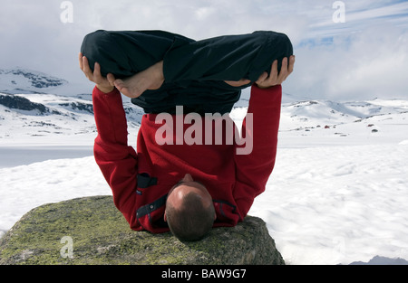 Doug Blane performing an Urdhva Padmasana yoga, upside down lotus on frozen Finse Vatn lake, Finse, Norway - Stock Image