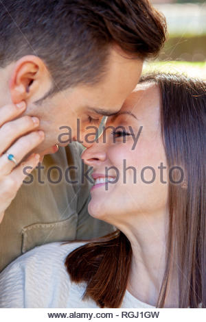 Young couple flirts romantically and intimately in a public park at daylight in an European city - Stock Image