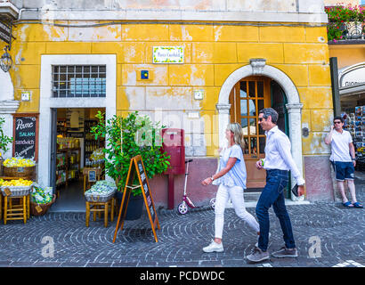 Man and woman walking down a cobble street in Limone, Italy. - Stock Image