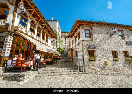 A server takes an order from a table of tourists in the old town center of the medieval city of Mostar, Bosnia and Herzegovina. - Stock Image