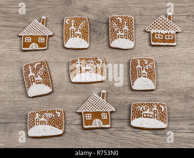 Group of ornate Christmas gingerbreads on wood background. Beautiful decorated gingerbread sweets in house shape and with hand-painted chapel in snow. - Stock Image