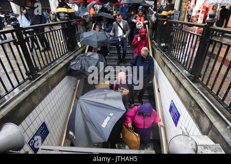 London, UK. 9th August, 2017.  Commuters walk into Oxford Circus underground station as heavy rainfalls hit London, UK. Credit: Ben Furst/Alamy Live News. - Stock Image