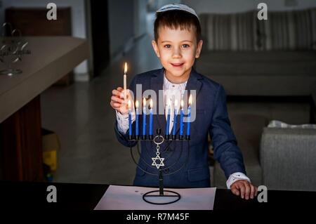 Cute Caucasian Jewish boy lighting candles on a traditional Hanukkah menorah candelabrum, Jewish holidays concept. - Stock Image