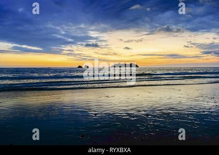 Dramatic Sunset Sky and Stormy Clouds over Pacific Ocean Coastline on Manuel Antonio National Park Beach in Costa Rica - Stock Image