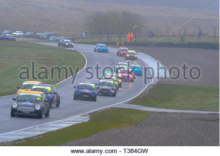Dunfermline, Scotland, UK. 7th April, 2019.  The pack enters Clark's during a Celtic Speed Mini Cooper Cup race at Knockhill Circuit. During a wet and misty opening round of the Scottish Championship Car Racing season organised by the SMRC (Scottish Motor Racing Club) at Knockhill. Credit: Roger Gaisford/Alamy Live News - Stock Image