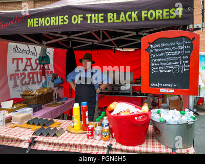 Gunthers Memories of the Black Forest a German man selling food  with several varieties of sausage from his stall at a North Yorkshire Food market - Stock Image