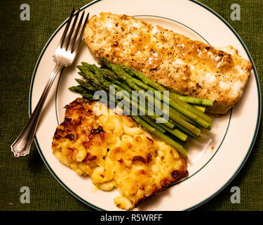 A hearty and healthy meal of a large piece of baked haddock, fresh asparagus, and baked mac and cheese on a white plate with a silver fork. - Stock Image