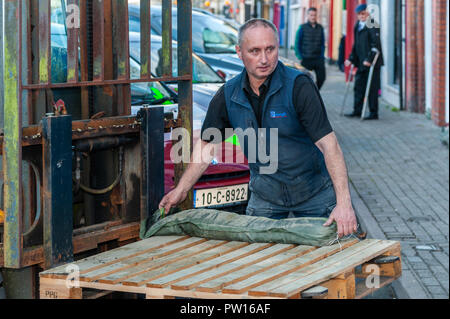 Bantry, West Cork, Ireland. 11th Oct, 2018. A member of Drinagh Hardware Store staff places sandbags outside the Drinagh store in preparation for the predicted Storm Callum, which is due to hit Ireland this evening. Credit: Andy Gibson/Alamy Live News. - Stock Image