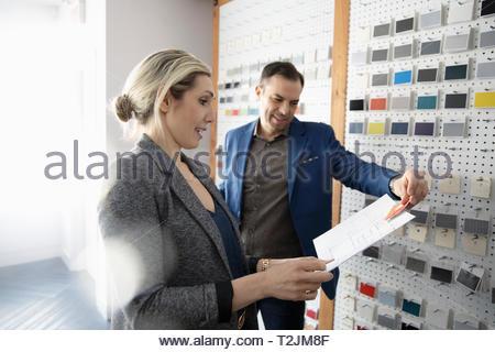 Interior designers reviewing blueprints in design studio - Stock Image
