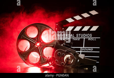 Vintage film claper with film reel and camera. filmmakers equipment background - Stock Image
