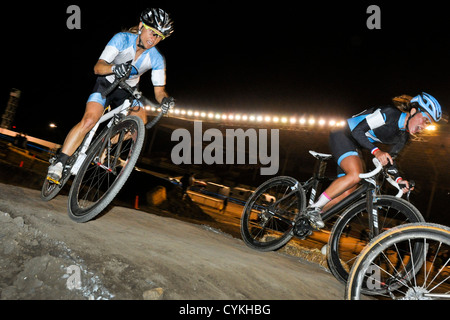 female bicycle racers on a cyclocross course at night in a stadium. - Stock Image