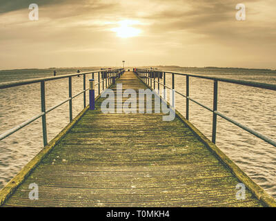 Sea bay, sun daylight relaxation landscape and wooden bridge view - Stock Image