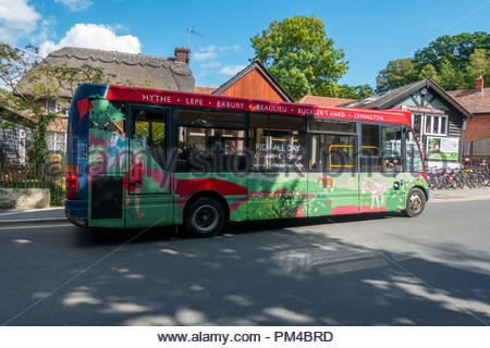 A decorated tourist bus stops for passengers in the village of Buckelt in the New Forest, Hampshire. - Stock Image