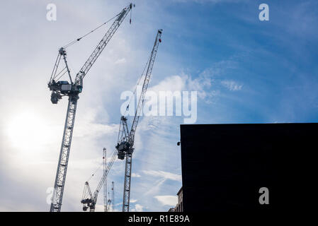 Silhouettes of three massive construction cranes with sky blue sky in the background - Stock Image