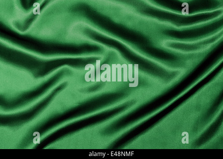 Green Silk background texture with wavy ripples to enhance the sheen of the fabric. - Stock Image