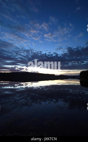 Clouds illuminated by the setting sun are reflected in a quiet lake. - Stock Image