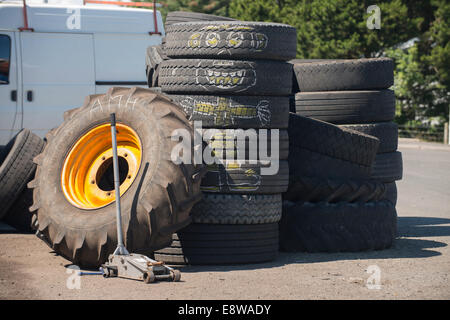 Old car tyres and a tractor wheel stacked outside a garage, a cartoon character chalk drawing appears on the old - Stock Image