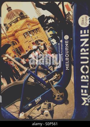 Melbourne's Flinders street station and bike rentals on bike rack in Melbourne Australia - Stock Image