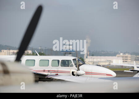 windows of Aeroflight Executive Services Piper PA-31-350 Navajo Chieftain parked and air-traffic control-tower behind - Stock Image