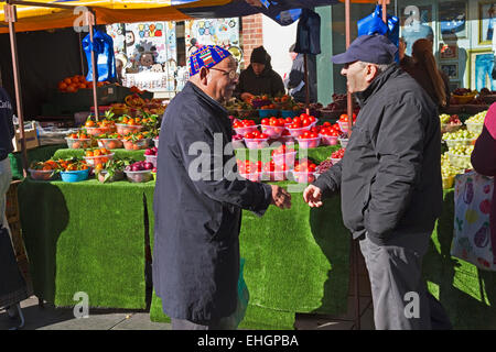 Two men meeting in front of fruit stall at St Albans Market, St Peters Street, St Albans, Hertfordshire, England, - Stock Image