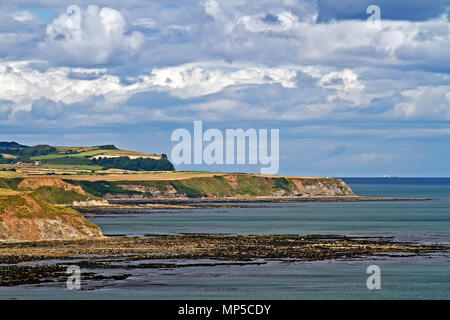 Views north along Scarborough's coast from the castle headland, of Jackson's Bay, Long Nab and the distant high ground of Rodger Trod. - Stock Image