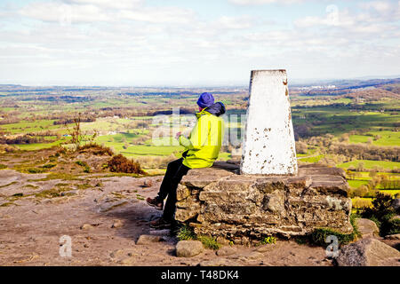 Man sitting enjoying the view over the Cheshire plain from the trig point on top of Bosley cloud or Cloud End near Congleton in Cheshire - Stock Image