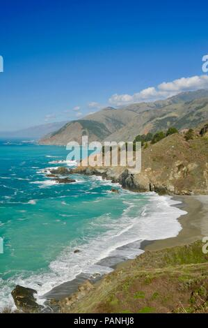 Popular Big Sur coastline with crashing surf, steep cliffs and along winding, curving Route Highway 1 crossing Bixby Creek Bridge, in California, USA. - Stock Image