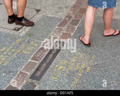 Two people standing either side of where the old Berlin Wall stood in Berlin Germany - Stock Image