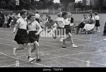 1950s, school sports, on a grass track, schoolgirls competing in the three-legged race, England, UK. - Stock Image