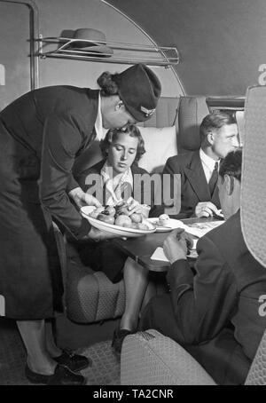 A Lufthansa stewardess serves a first-class passenger. - Stock Image