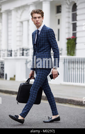 Young man in blue checked suit walking across the road - Stock Image