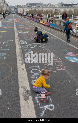 Shildren draw on the road as Climate Change activists with Extinction Rebellion campaign for a better future for planet Earth after blocking Waterloo Bridge and as part of a multi-location 5-day Easter protest around the capital, on 16th April 2019, in London, England. - Stock Image