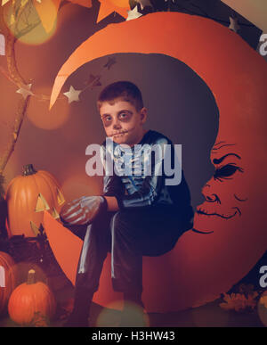 A boy is wearing a Halloween Skeleton costume and sitting on an orange moon with a face and stars for a night portrait. - Stock Image