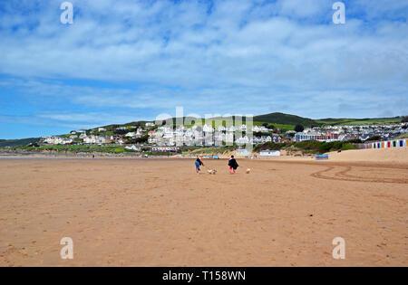 Two ladies walking dogs on Woolacombe Beach, Woolacombe Bay, Devon, UK - Stock Image