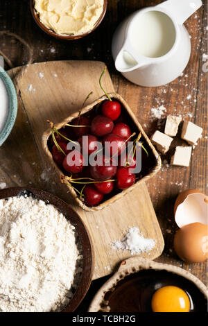 high angle view of the ingredients to prepare a coca de cireres, a cherry sweet flat cake typical of Catalonia, Spain, such as wheat flour, milk, suga - Stock Image