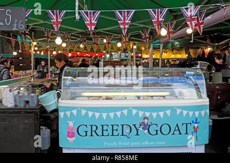 Borough Market food stall sign Greedy Goat goats milk ice cream refrigeration unit and worker with Union Jack bunting London England UK  KATHY DEWIT - Stock Image